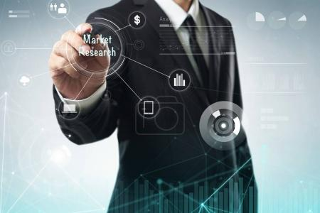 "Businessman draw ""Market Research"" word on digital virtual screen . Hi-tech business concept ."