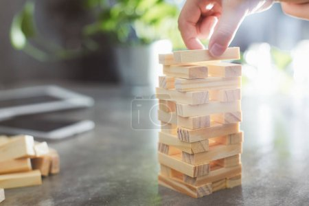 Photo for Hand of kid playing a blocks wood tower game of architectural project with sun flare and blur background .Selected focusing . - Royalty Free Image