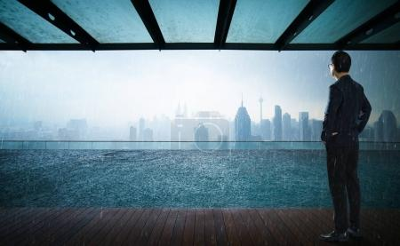 Businessman looking and thinking front of a Swimming pool on roof top with beautiful city skyline view,rainin