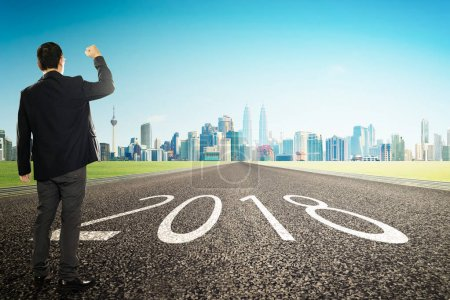 2018 new year ,young businessman cheer with city skyline background . Refresh and hope concept .