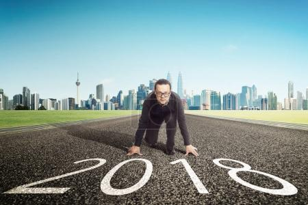 Photo for New year 2018 ,young businessman starting position to his career with city skyline background . Determined to start concept . - Royalty Free Image