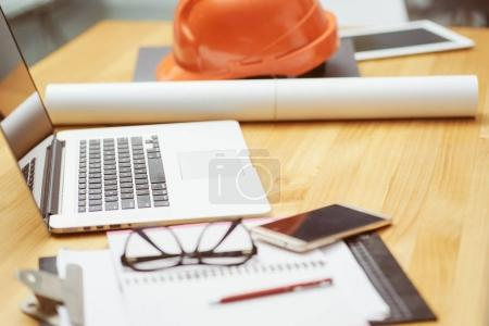 Laptop ,glasses, note book ,phone ,blueprint and orange safety helmet stacking on table at construction site for Engineer, foreman and worker , selective focusing .