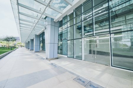 Modern empty office building with glass wall and empty pavement .