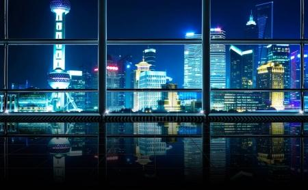 Modern empty and clean office interior with glass windows , shanghai pudong city skyline background , night scene .