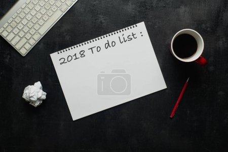"""Keyboard, pen and other supplies with cup of coffee with text """" 2018 to do list"""". Wooden black office desk table with top view angle ."""