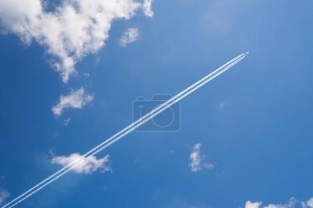 Airplane contrail against skyblue sky with white cloud .