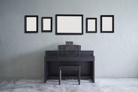 Room with five empty picture frames and black piano on grey background