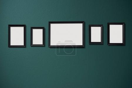 Five empty pictures frames hanging on green color wall background
