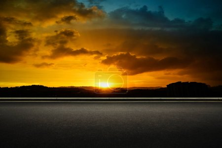 Asphalt road side with dramatic blue and orange color cloudy sunset golden hour .