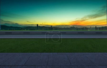 Photo for Side angle view empty asphalt road with grass ,stone marble floor and sunrise background . Mixed media . - Royalty Free Image