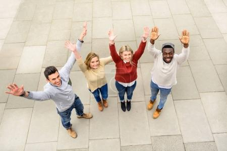 Photo for Group of different countries best friends put hands up together like one work team spirit. Top view of multiracial happy people with raised arms outdoor and sharing time. Students friendship concept. - Royalty Free Image