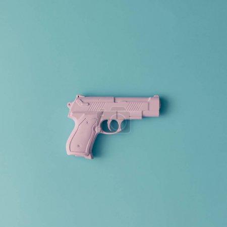 Photo pour Une arme de poing rose sur fond pastel bleu - image libre de droit