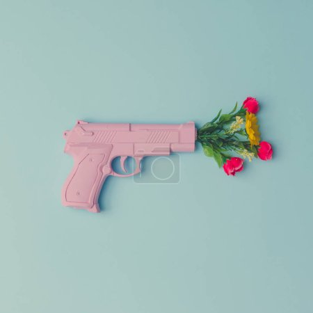 Photo for Pink hipster handgun on blue pastel background with flowers - Royalty Free Image