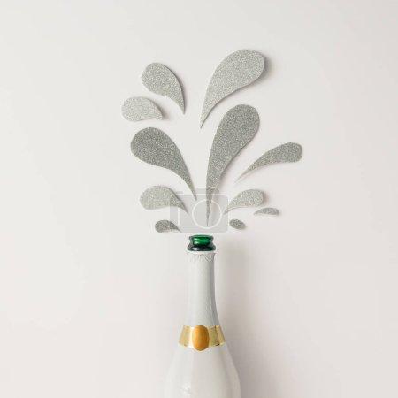 Foto de Botella de champán con salpicaduras brillantes plateadas sobre fondo blanco. Concepto de fiesta mínima - Imagen libre de derechos