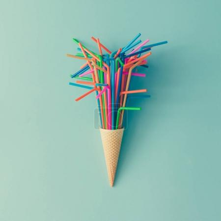 Photo for Ice cream cone with colorful drinking straws on bright blue background. Minimal food concept - Royalty Free Image