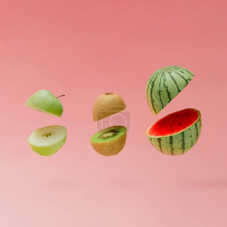 Photo pour Tranche de pastèque avec pomme et kiwi sur fond rose pastel. Concept de fruit minimal - image libre de droit