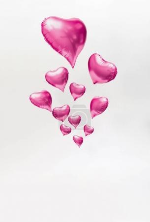 Foto de Corazón de color rosa en forma de globos flotando sobre fondo claro, amor mínimo concepto - Imagen libre de derechos