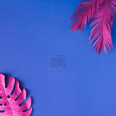 Photo for Tropical and palm leaves in pink colors on blue background, Concept art, Minimal surrealism - Royalty Free Image