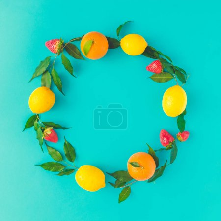 Creative summer layout made of lemons, oranges and strawberies on pastel blue background. Fruit minimal concept. Flat lay.
