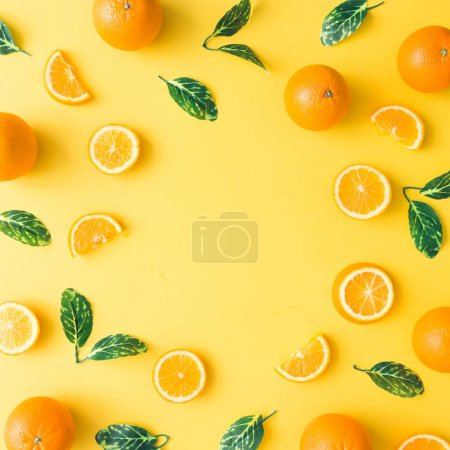 Photo for Creative summer pattern made of oranges and green leaves on pastel yellow background. Fruit minimal concept. Flat lay. - Royalty Free Image