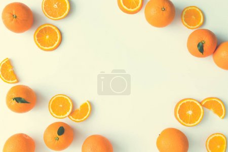 Creative summer layout made of oranges and green leaves on bright background. Fruit minimal concept. Flat lay. Border with copy space.