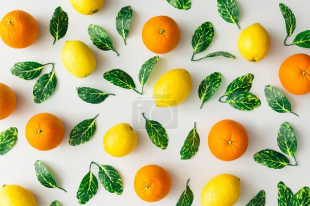 Creative summer pattern made of oranges, lemons and green leaves on bright background. Fruit minimal concept. Flat lay.