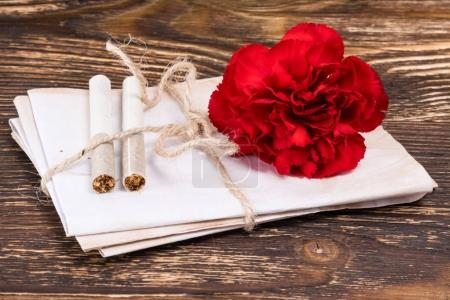 On a wooden table, bandaged documents and two cigarettes next to a carnation