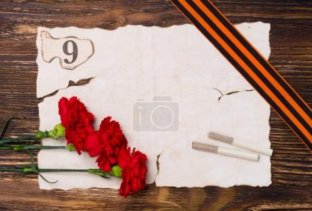 Vintage background for a victory day postcard, with a red carnation, two cigarettes and a 9 digit