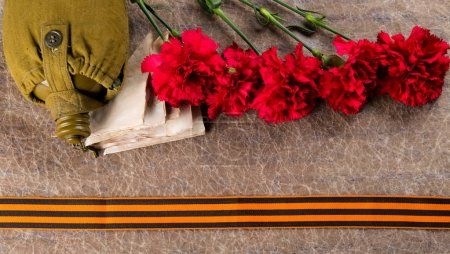 red carnations flowers, letters on the surface of military cloth with a St. George ribbon and a jar