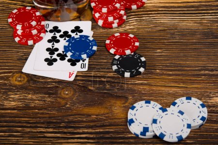 the layout of cards and poker chips, on a wooden background