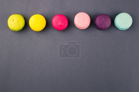 Colourful french macaroons on the grey background, Top view