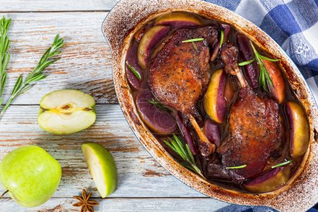 two roasted duck legs grilled  in red wine and apple
