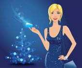 Beautiful blonde woman wearing elegant blue dress holding a credit card stands near Christmas tree