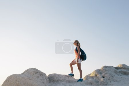 Young woman hiker with backpack standing on cliff and looking forward. lady tourist on top of a mountain enjoying view before sunset