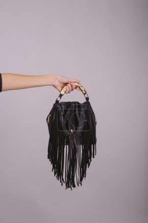 woman holding a leather bag on a gray background. cropped image of a female hand holding a black bag with fringe. close up