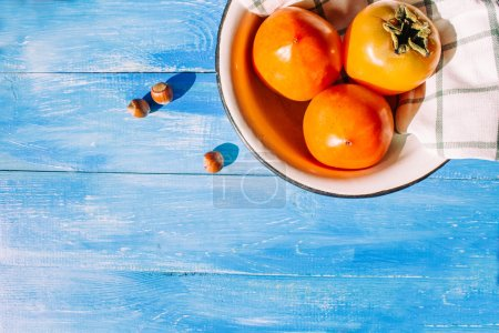 Ripe persimmon is in a bowl with a cloth napkins on a blue background, near lies group of brown hazel nut. Vegetarian nutrition. Vegetarian nutrition. Healthy eating, dieting