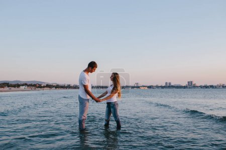 couple holding hands in the sea