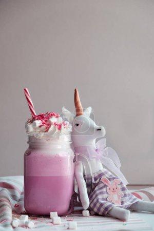Toy unicorn and pink milk shake