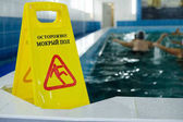 Yellow plastic sign by swimming pool. Copy space. Pool in nursing home