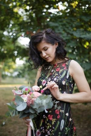 brunette young woman in floral spring summer dress. Girl posing with flower bouquet. Summer floral outfit. Stylish wavy hairstyle. Fashion photo.