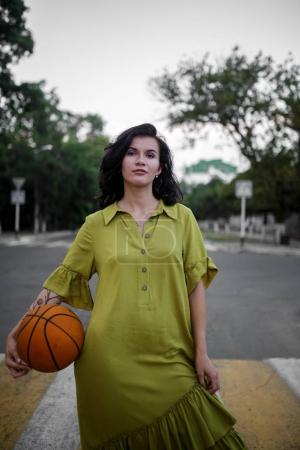 brunette young woman in green spring summer dress with ball for basketball. Girl posing on street. Fashion photo.