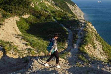 beautiful brunette woman walking hills near blue sea. Female tourist with backpack on hill near ocean. Traveling, freedom and active lifestyle concept