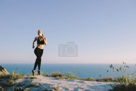 young attractive sport woman running on country road near sea.  girl teenager on workout outdoor.  jogging, training, fitness, healthy lifestyle, sports and wellness concept