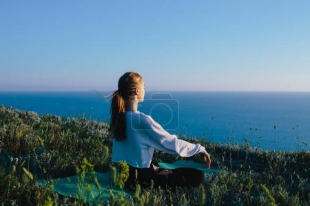 Young Woman Practicing Yoga In The Lotus Position outdoor. teenager girl relaxing on hill near sea. Concept of calm, meditation, jogging, training, relax, healthy lifestyle and wellness