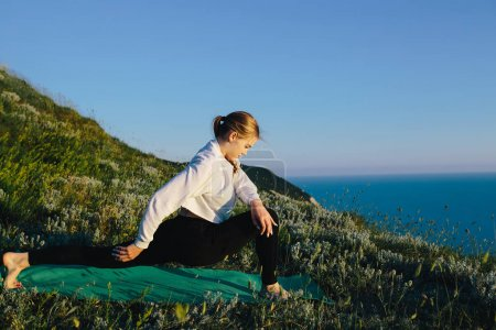 young attractive sport woman training, stretching on hill near sea.  girl teenager on workout outdoor.  training, fitness, healthy lifestyle, sports and wellness concept