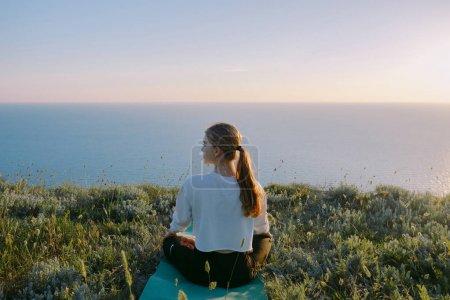 Photo pour Jeune femme pratiquant Yoga dans la Position du Lotus extérieure. fille adolescente reposante sur la colline du bord de mer. Concept de calme, méditation, jogging, formation, détente, bien-être et style de vie sain. vue arrière - image libre de droit