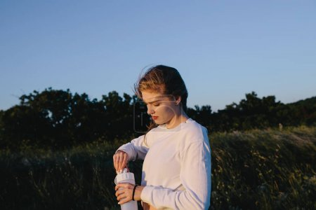 Foto de Mujer deporte joven con botella de agua después del entrenamiento en colina cerca de mar. adolescente chica con bebidas en la naturaleza. salir a correr, entrenamiento, fitness, estilo de vida saludable, deportes y bienestar concepto - Imagen libre de derechos