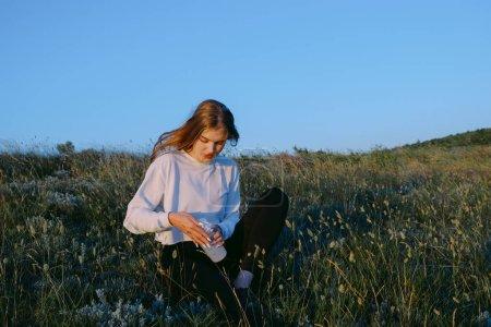 Photo pour Jeune femme sportive avec bouteille d'eau après s'être entraînée sur une colline près de la mer. fille adolescente avec boisson sur la nature. jogging, entraînement, fitness, mode de vie sain, sport et concept de bien-être - image libre de droit