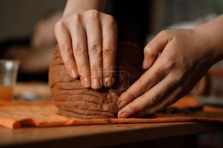 Woman's hand making clay pot on the pottery workplace. Ceramist modeling on pottery workshop. Close up