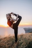 young sport woman training, stretching on hill near sea.  girl teenager doing yoga exercise, workout outdoor on sunset .  jogging, training, fitness, healthy lifestyle, sports and wellness concept